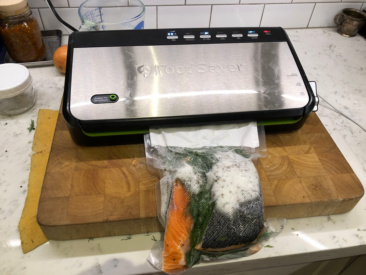 The assembled gravlax being vacuum sealed.