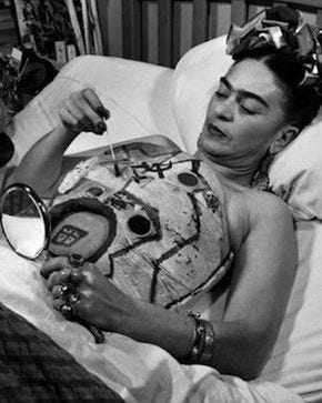 Image of Frida Kahlo painting and examining her chest cast