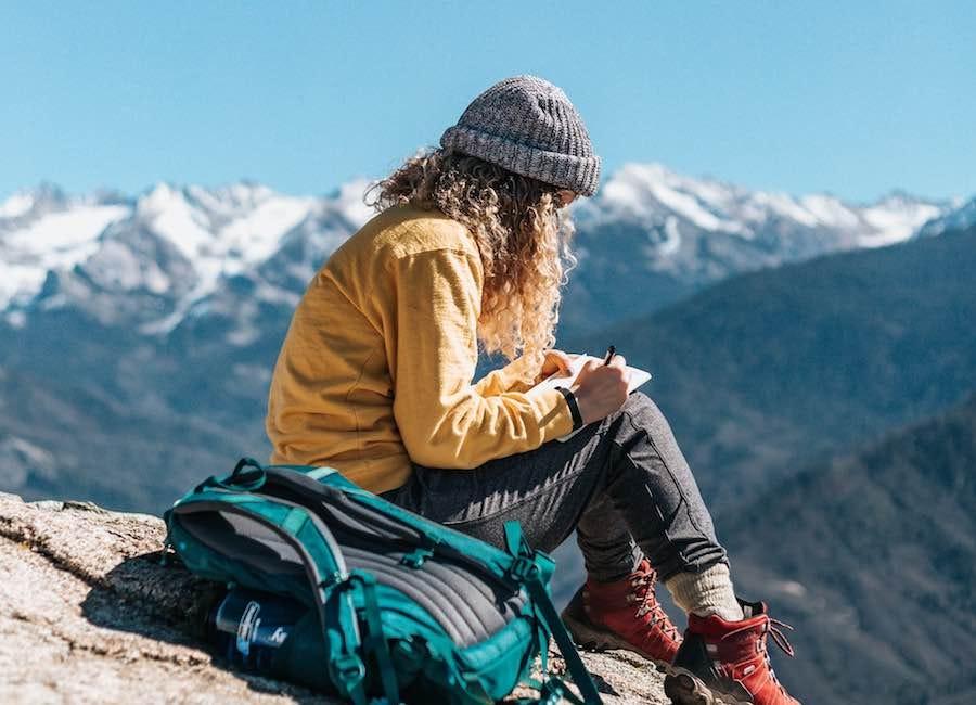 Woman writing in journal during mountain hike