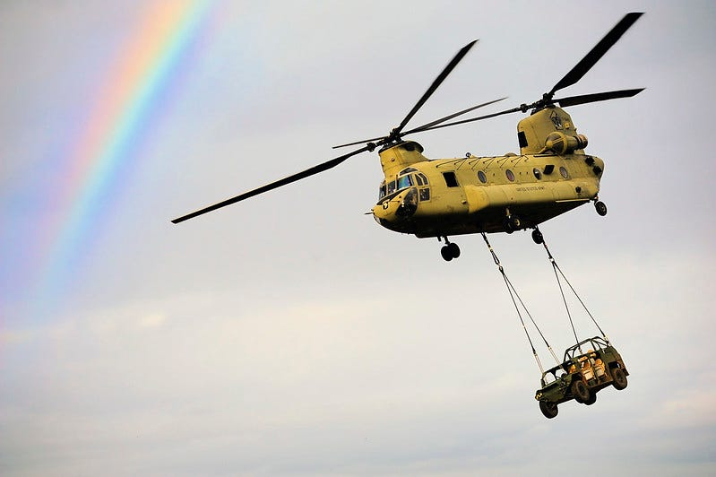 CH-47 Chinook carries Humvee with a rainbow in the background