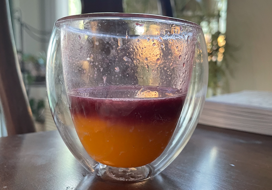 Clear glass on a table with orange juice and some red-colored juice on top.