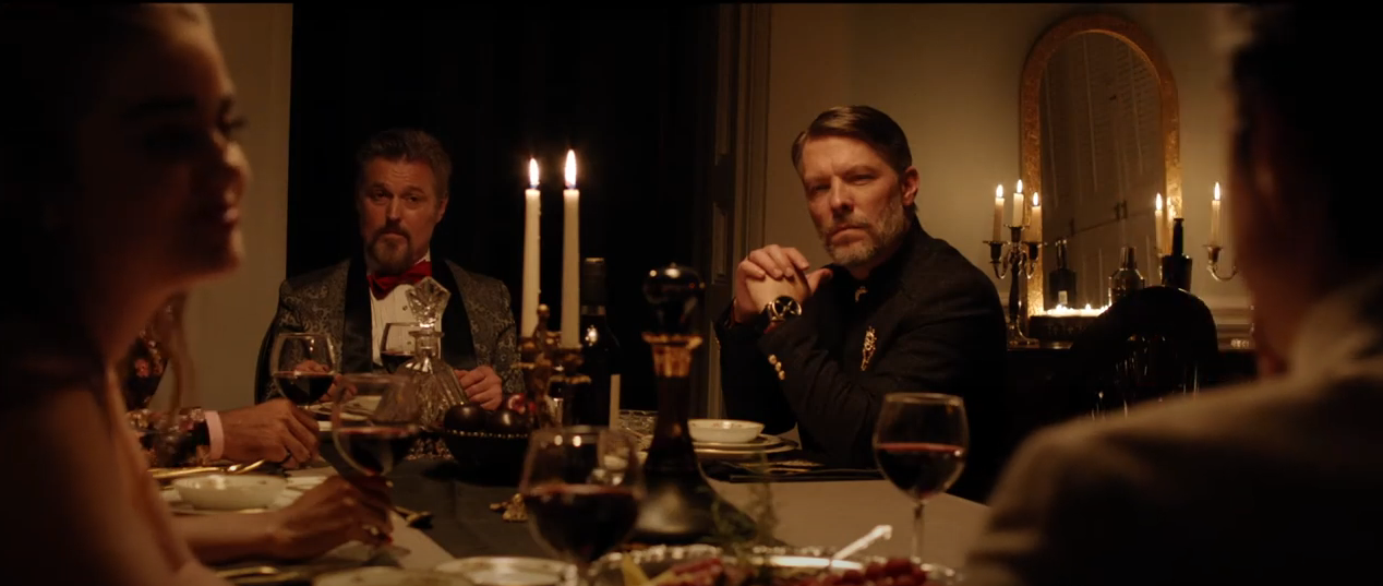 From the film 'The Dinner Party': Two men stare inquisitively and ominously, across a fine dining table, from a woman on the left of the screen, looking at her husband on the right.