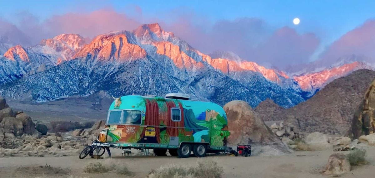 handpainted airstream sits in front of mountain range at sunset