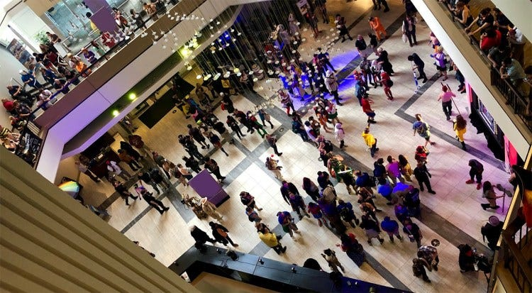 Photo looking down at a hotel lobby full of people at a convention
