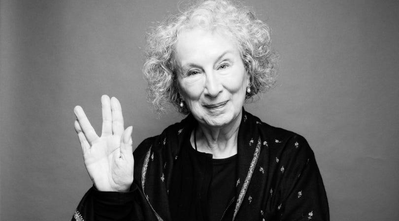 fotografia da autora Margaret Atwood em preto e branco. Uma senhora de cabelos bem brancos e cacheados, sorrindo e fazendo com a mão direita o sinal da saudação vulcana de star trek