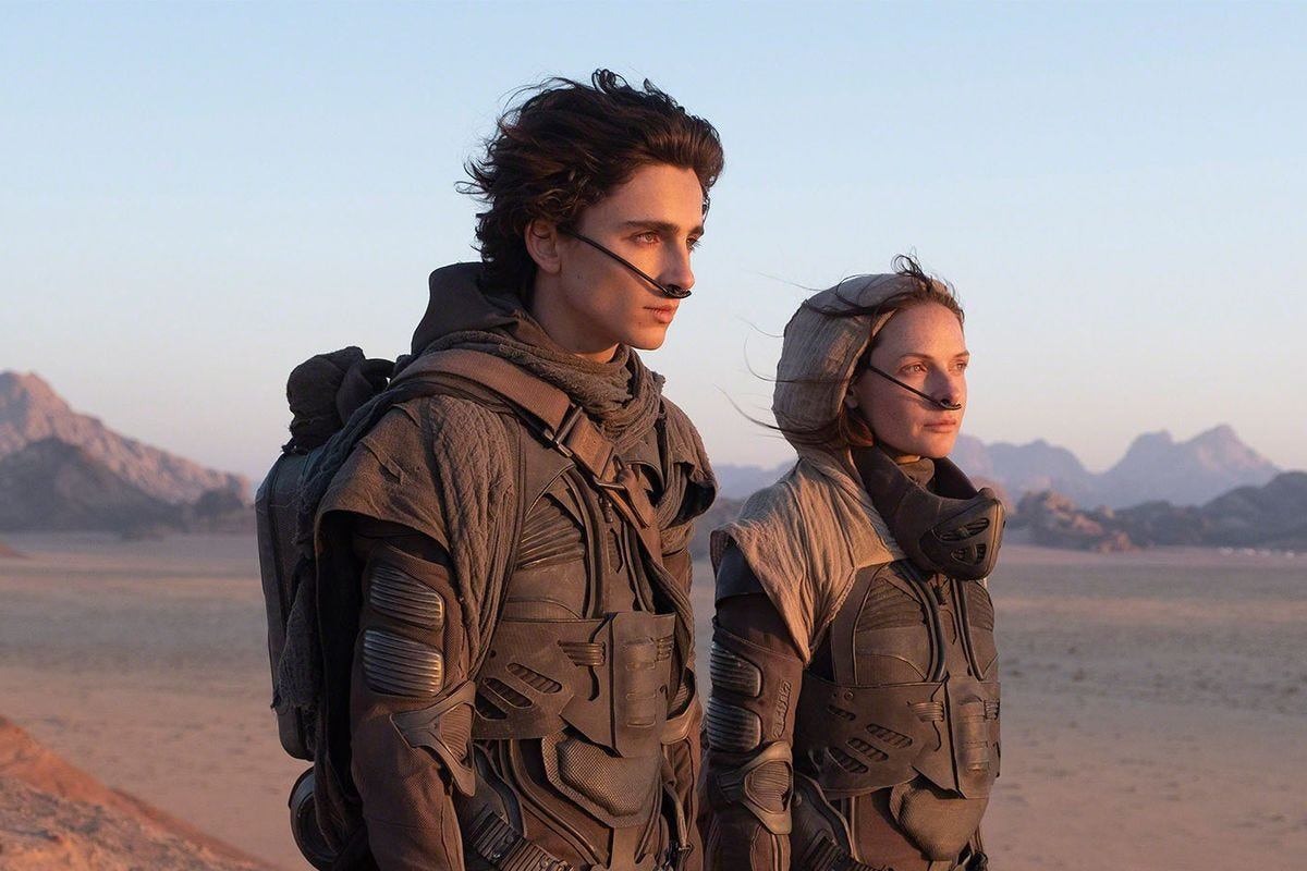 Timothée Chalamet as Paul Atreides and Rebecca Furguson as Lady Jessica Atreides stand in the desert on the set of Denis Villenueve's Dune.