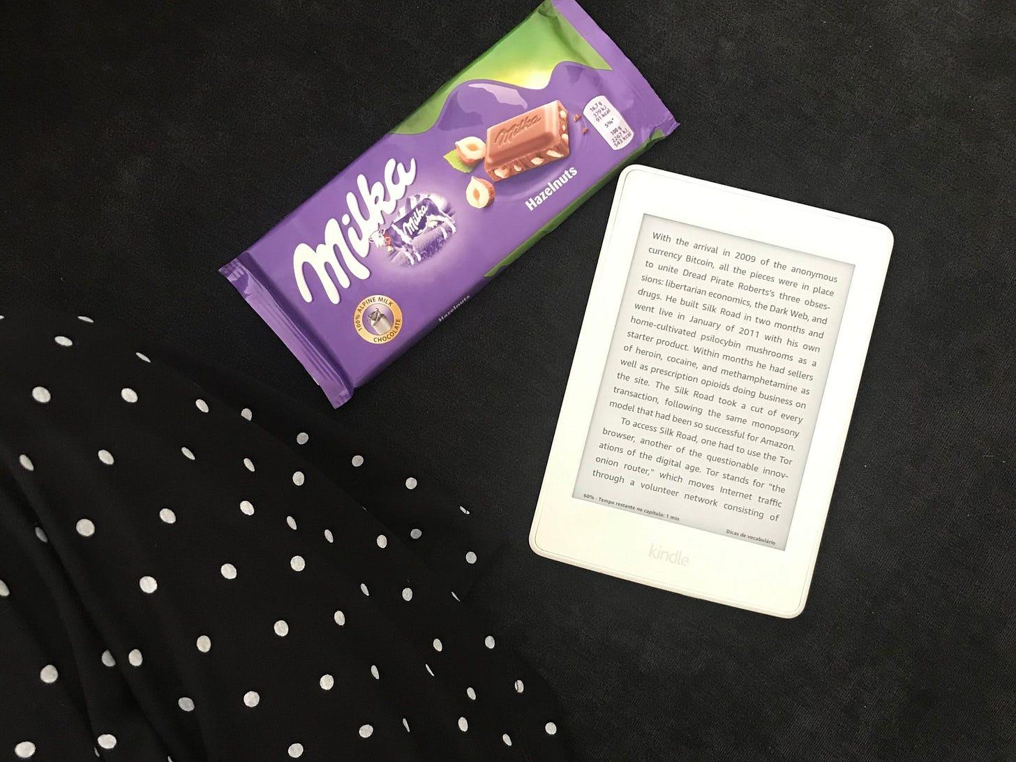 uma foto tirada de cima, de uma pessoa de pernas cruzadas com uma barra de chocolate milka e um kindle paperwhite branco mostrando uma página aleatória de um livro.