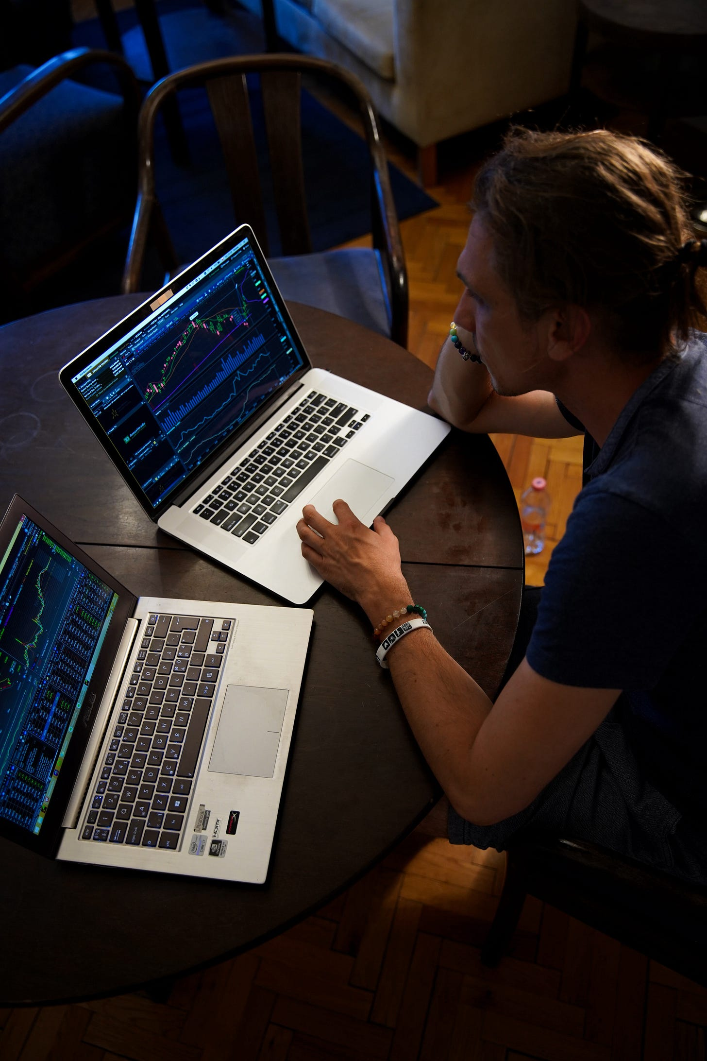 A man sitting in front of two laptops with stock charts and market data open. He's browsing different stocks on each of the laptops.
