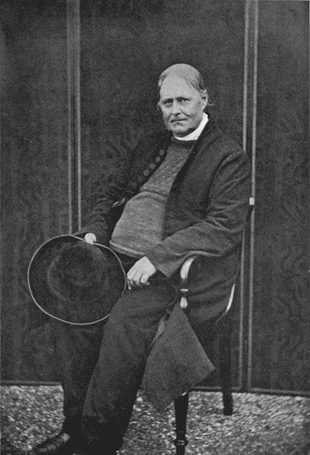 A black and white portrait of a middle-aged man, sitting in a chair, holding his had in his hand. He wears a formal jacket over a fisherman's sweater, and stares directly at the camera.