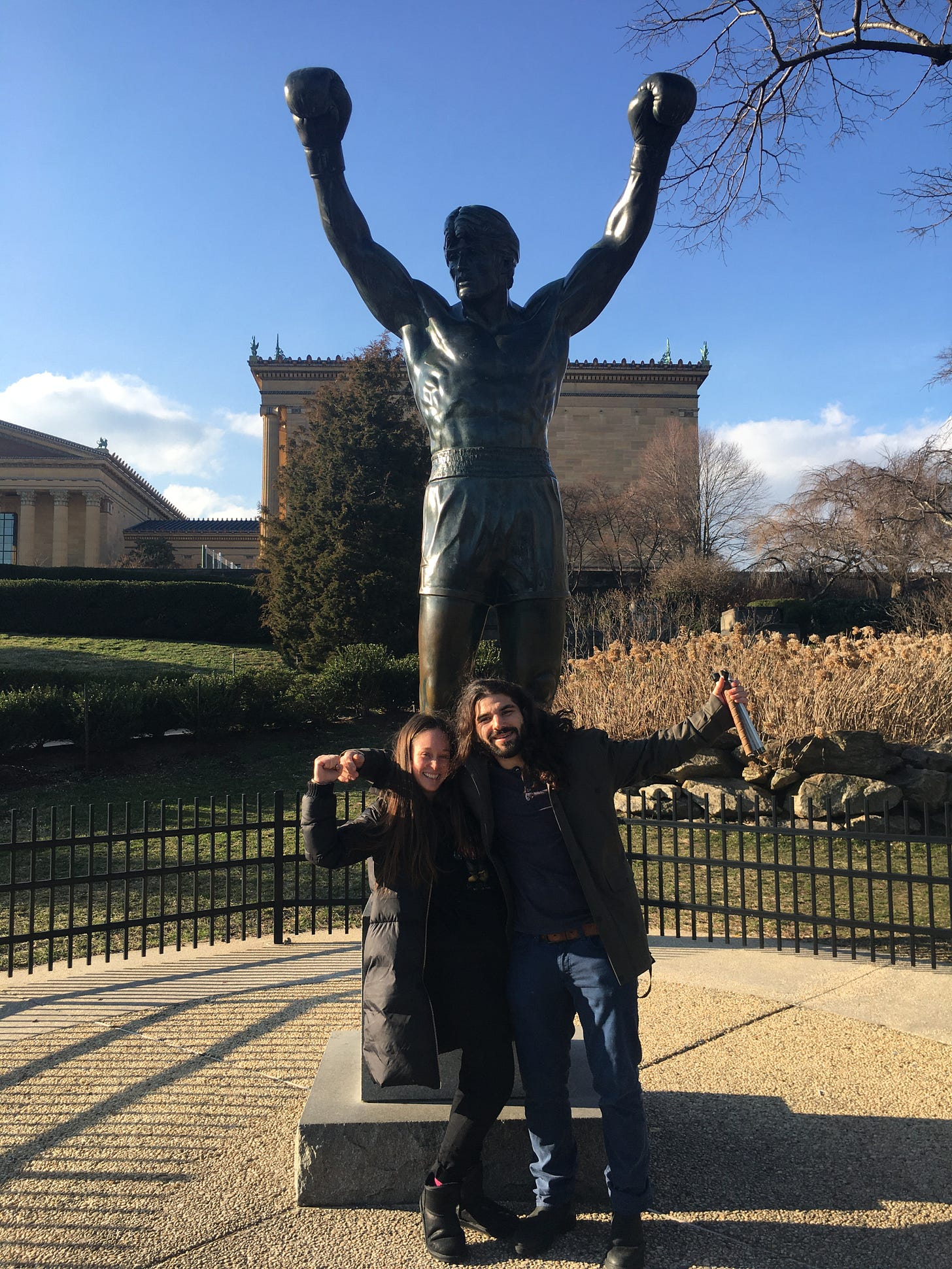anthony and kelly stand in front of the rocky statue in philly