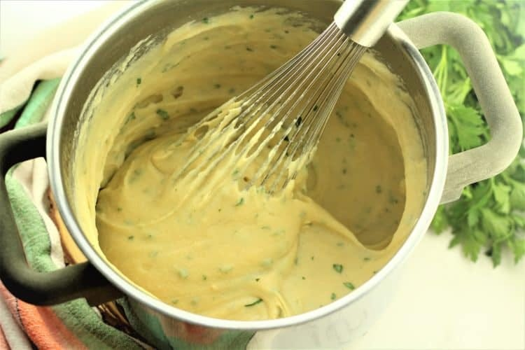 cooked panelle mixture in a sauce pan with whisk and parsley on side