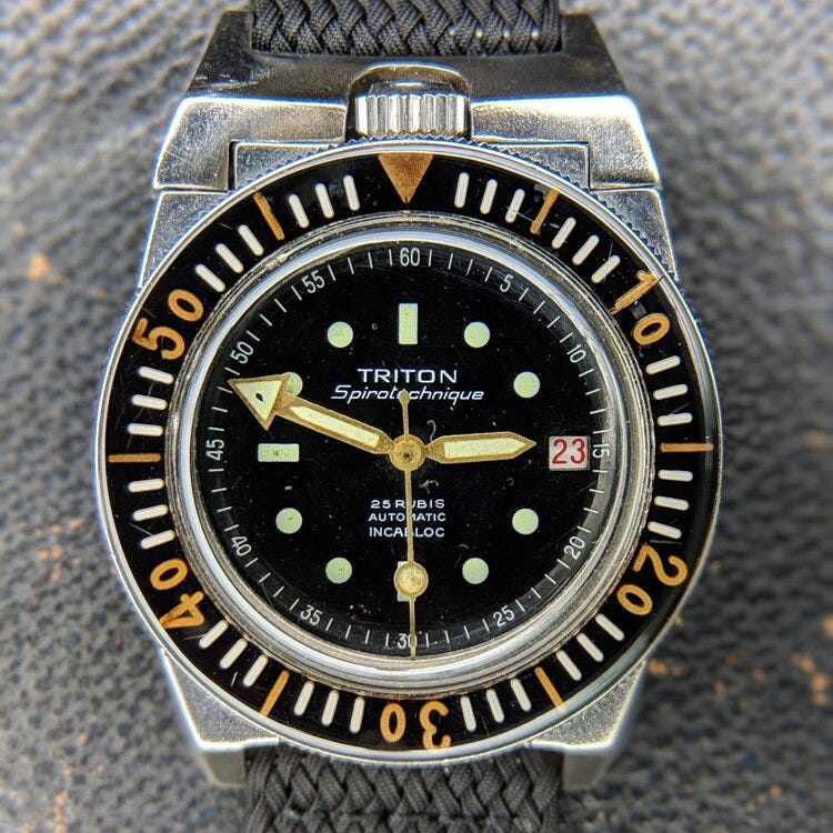 © WATCHISTRY | Spirotechnique was a diving equipment brand founded by Jacques Cousteau; its Triton watch was developed in the early 1960s to professional diving and military standards. This particular example was issued to the  RHIN , a submarine support vessel in service from 1964-2002; during a service, this Triton received a replacement Rolex crown.