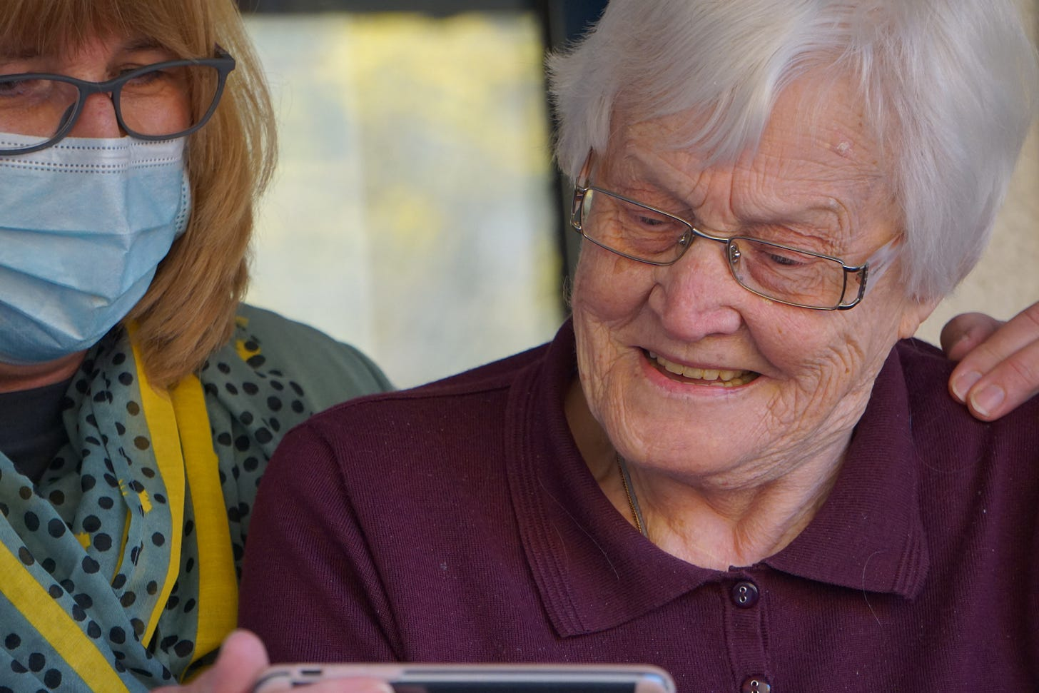 nurse with mask showing elderly woman an iphone