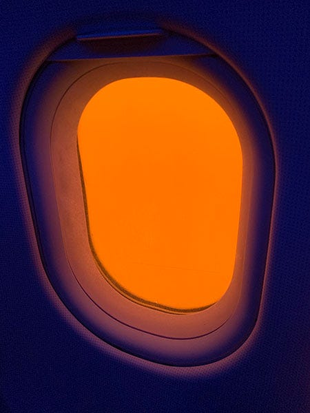 A photo of a window on an airplane where the wall is dark purple and the window is only orange.