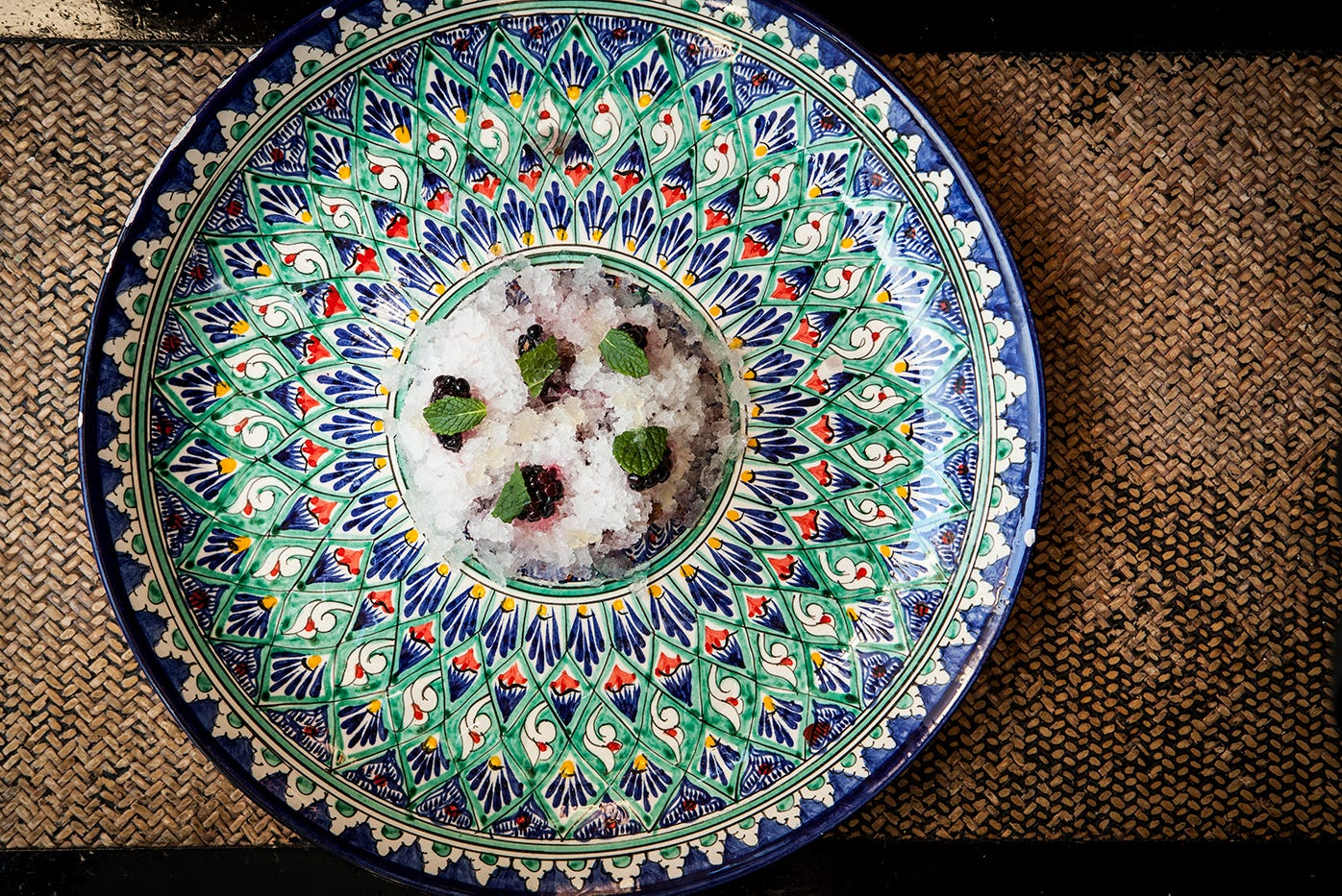 An overhead of photo of a large colourful plate on a rattan mat. In the centre of the plate is a pile of granita, decorated with black mulberries, mint leaves and pieces of mochi.
