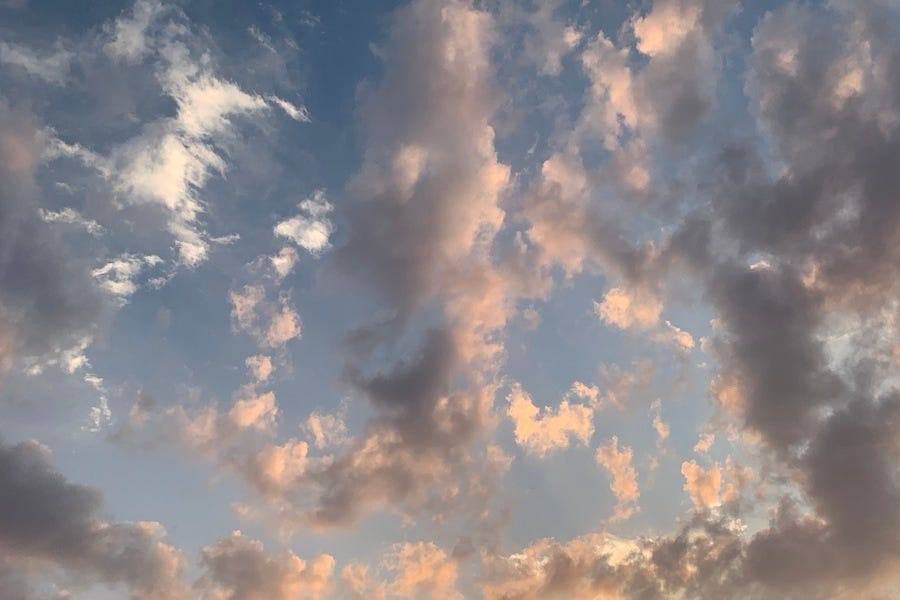 A blue sky filled with a jumbled assortment of clouds like short brushstrokes in white, gray, gold, and pink.