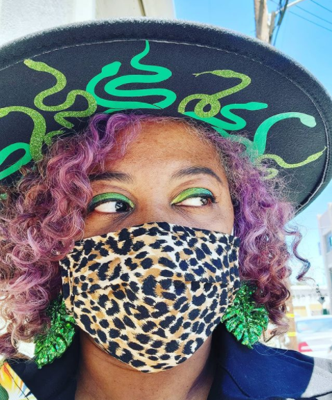 close-up photo of me. I am wearing a leopard print face mask. I have green eyeshadow and large green glittery monstera earrings. I am wearing a wide brimmed black hat that has prints of green snakes on the under side of the brim.