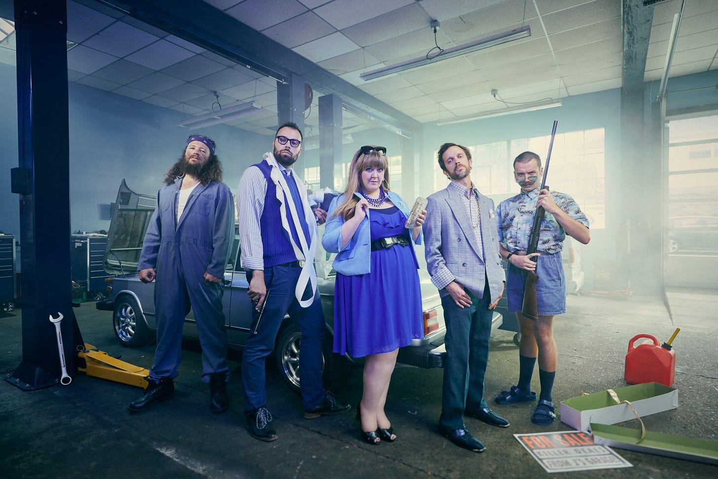 group shot of comedians in a mechanics garage