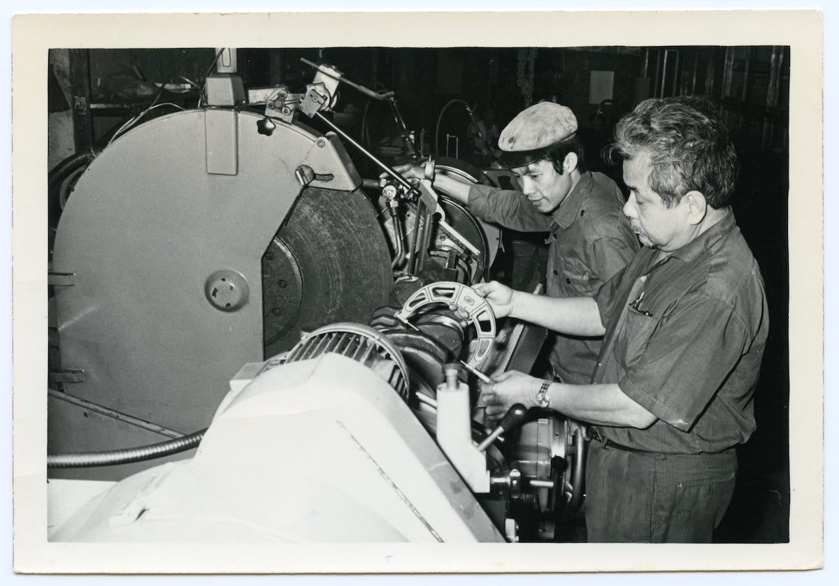 A black and white photo of my grandfather machining a part next to one of his employees