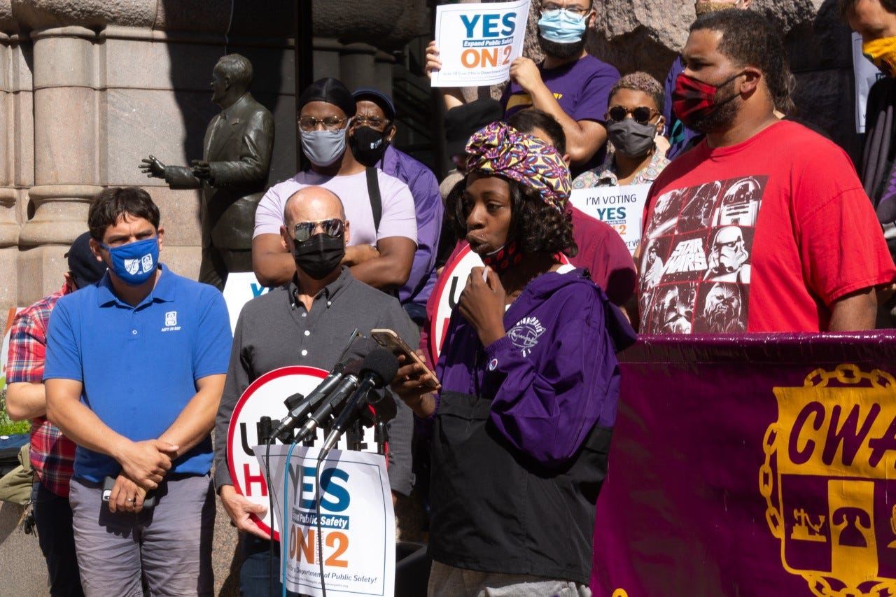 Lexi Collins, a Black woman wearing a purple and black windbreaker and purple and yellow headscarf addresses a crowd in front of a group of people