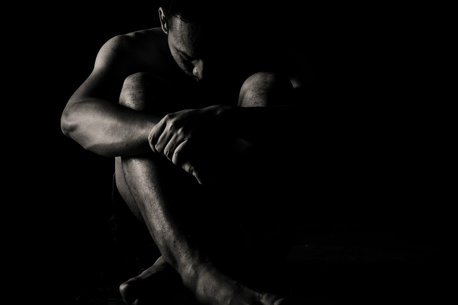 black and white photo of a depressed man crouched in the dark for article by Larry G. Maguire