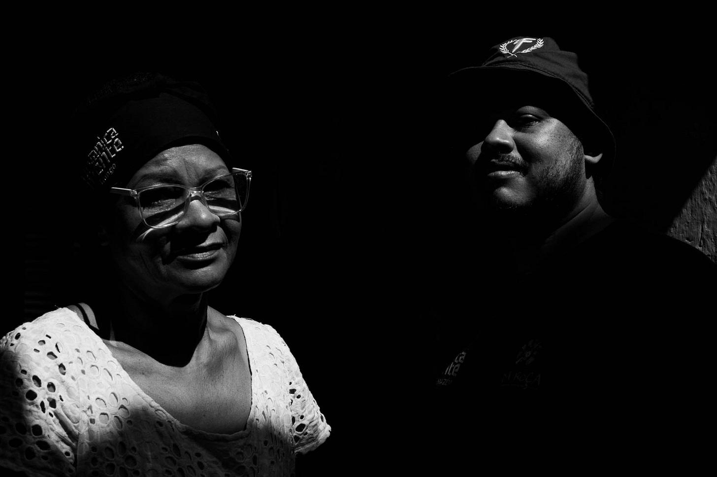 Imagem em preto e branco mostra tia Nice, usando óculos e vestindo camisa branca rendada, ao ldo do flho Thiago Vinicius, de boné e camiseta preta