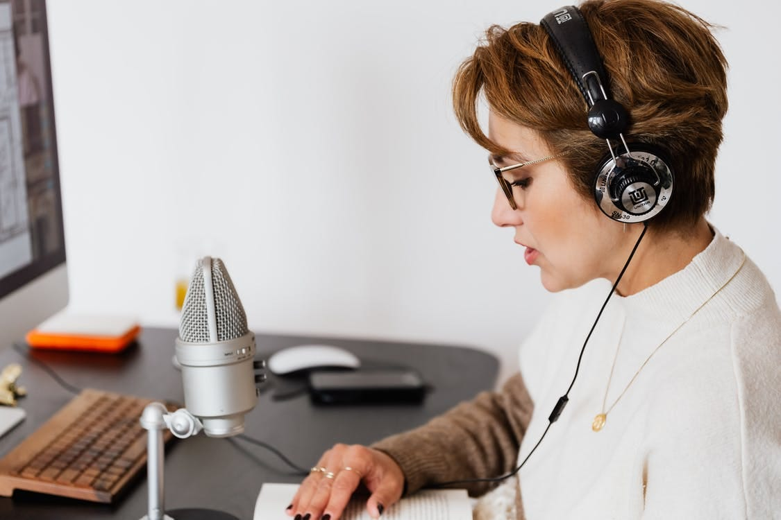 Photo of Woman Reading a Book While Wearing Headphones