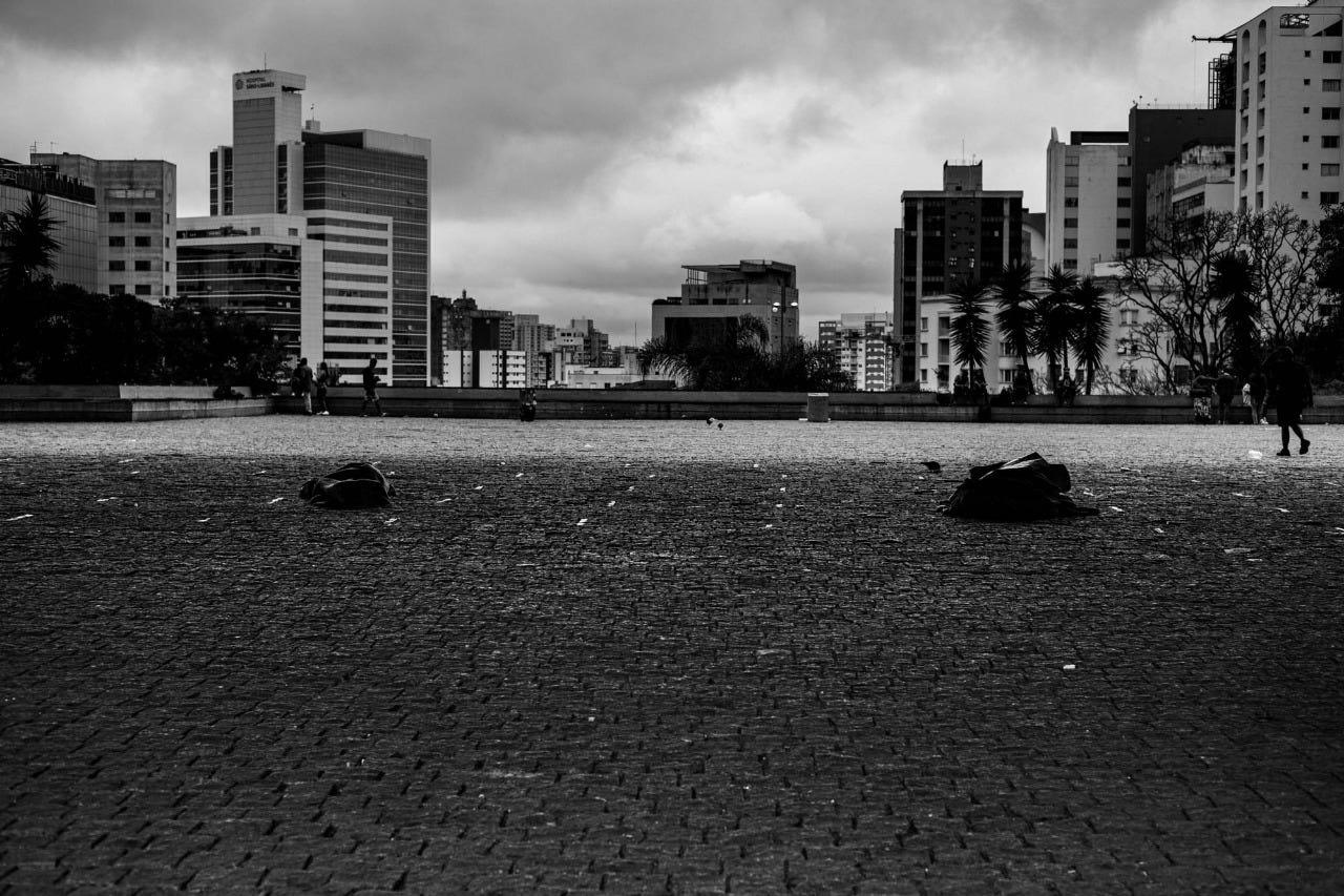 Imagem em preto e branco mostra vão do MASP, na Avenida Paulista, onde pessoas dormem no chão