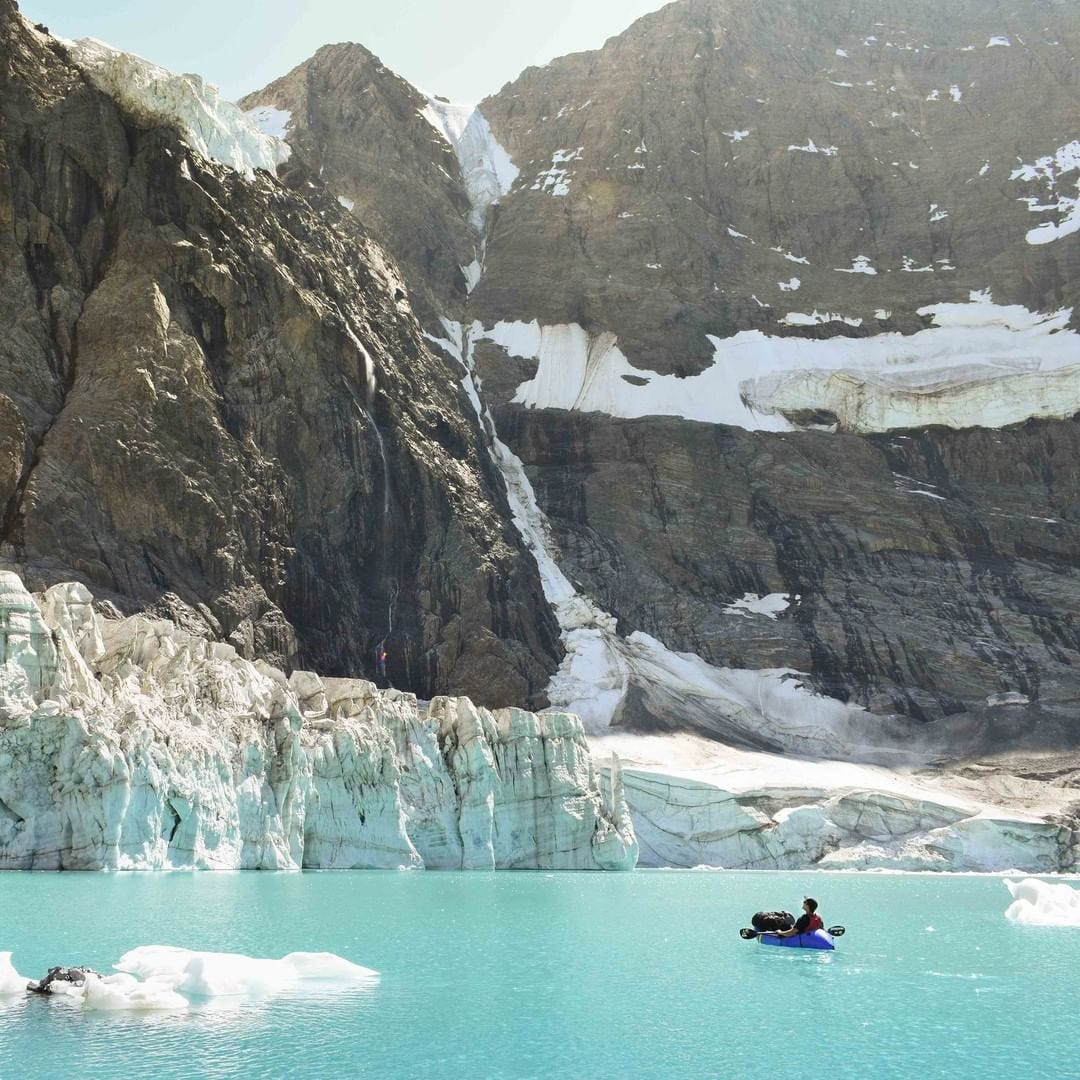 kayak at the base of a glacier in water