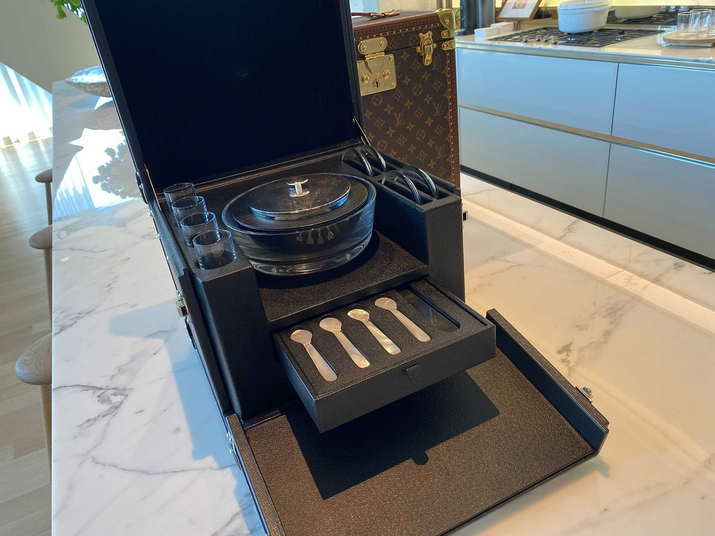 The caviar trunk is a matte black cube, top lid tilted up and front folded down to reveal a drawer of caviar spoons, and a bowl, presumably to hold the caviar. It sits on a shiny marble countertop and looks insanely wealthy.