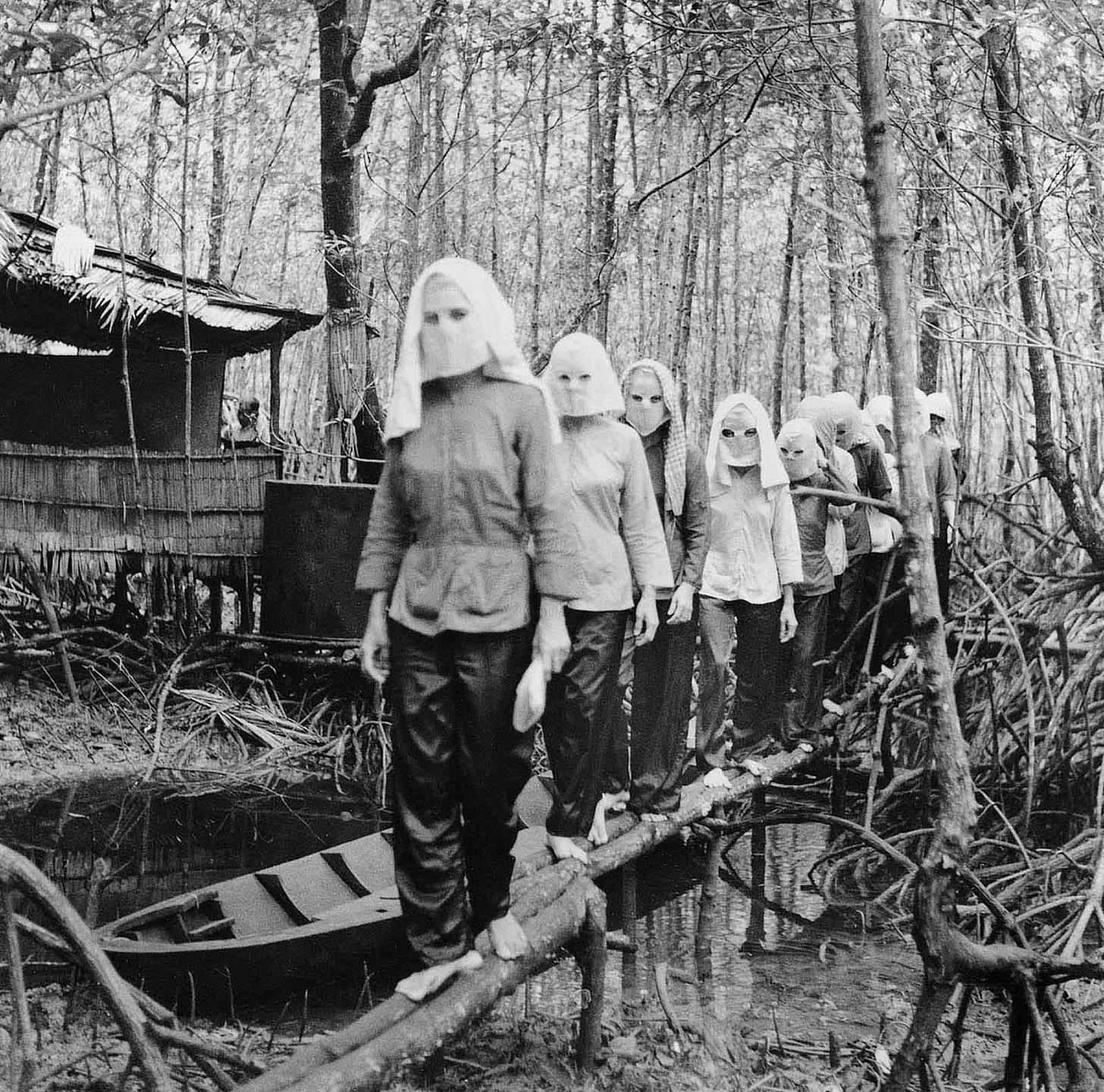 """Activists meet in the Nam Can forest, wearing masks to hide their identities from one another in case of capture and interrogation. From here in the mangrove swamps of the Mekong Delta, forwarding images to the North was difficult. """"Sometimes the photos were lost or confiscated on the way,"""" said the photographer. 1972. (Photo by Vo Anh Khanh)."""