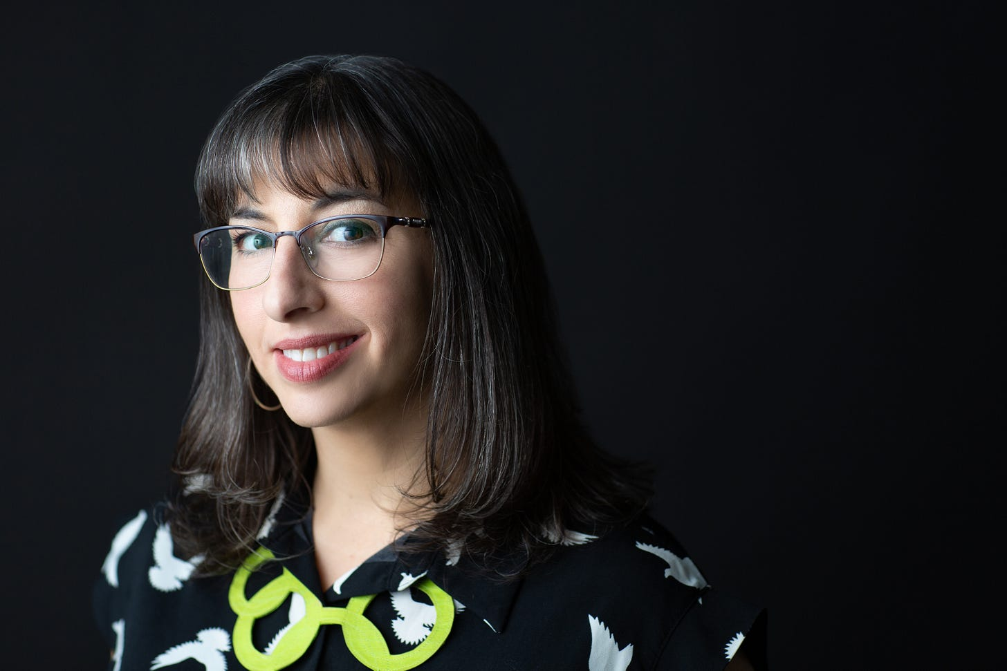 Photo of brown-haired female rabbi with bangs, glasses, wry smile