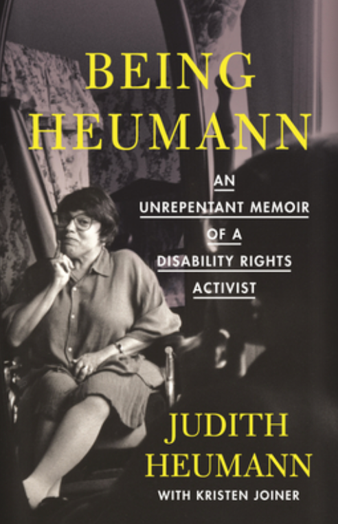 Book cover of Being Heumann: An Unrepentant Memoir of a Disability Rights Activist, by Judith Heumann with Kristen Joiner. Cover photo shows a smartly dressed middle-aged woman with brown hair and glasses wearing a skirt and collared shirt sitting in a wheelchair with crossed legs. She has a knowing smile on her face and her one hand is resting below her chin.