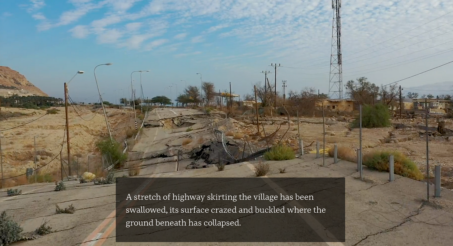 """Screenshot from a drone video showing an undermined road pocked with sinkholes. A text overlay reads """"A stretch of highway skirting the village has been swallowed, its surface crazed and buckled where the ground beneath has collapsed."""""""