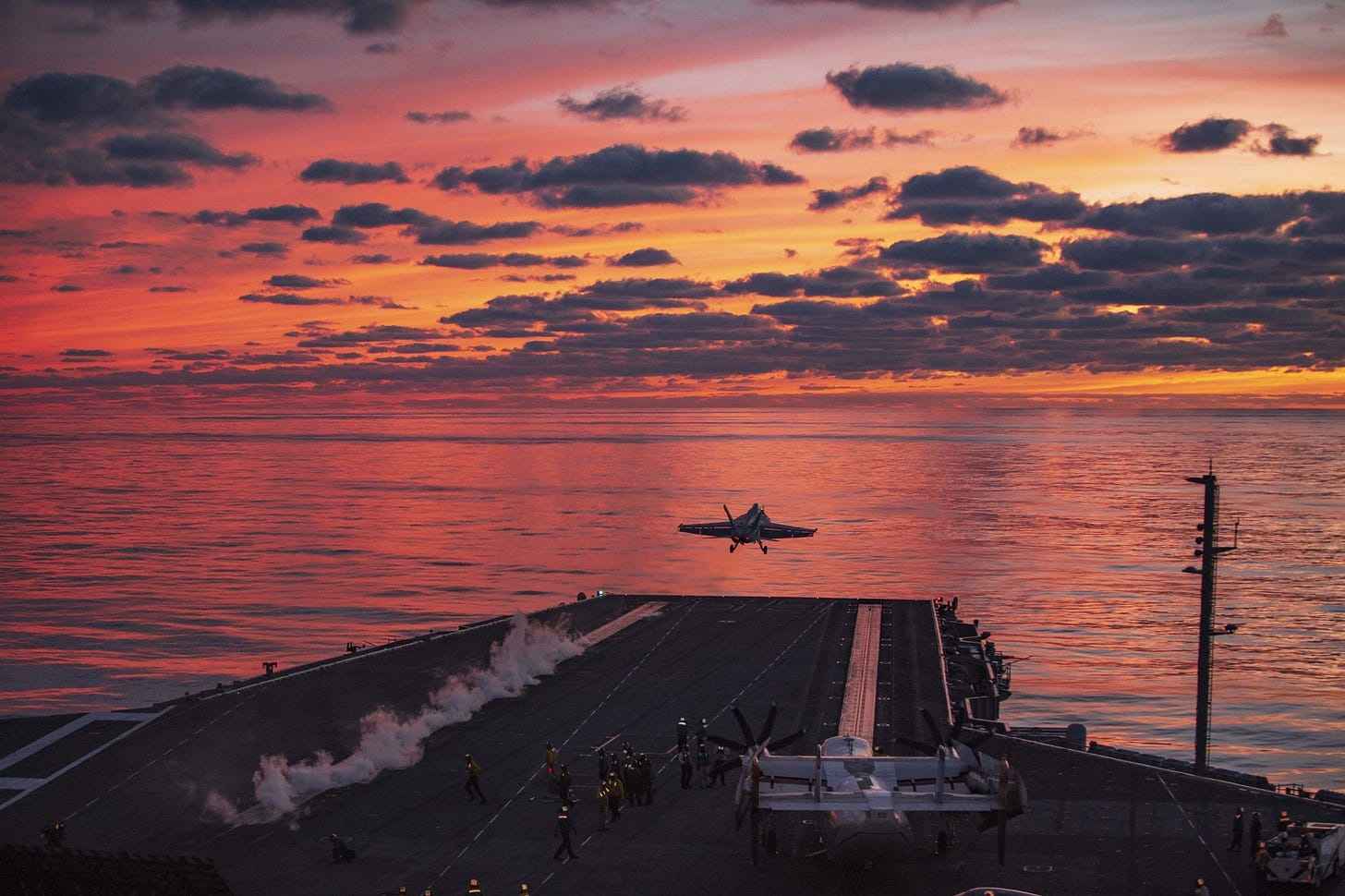 A plane flies off the deck of the Eisenhower carrier, leaving a small trail of steam.