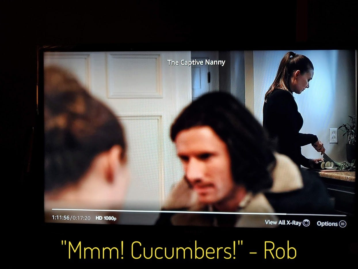 """Emily slicing cucumbers in the background while Chloe and Rob talk in the foreground, captioned """"Mmm! Cucumbers!"""" - Rob"""