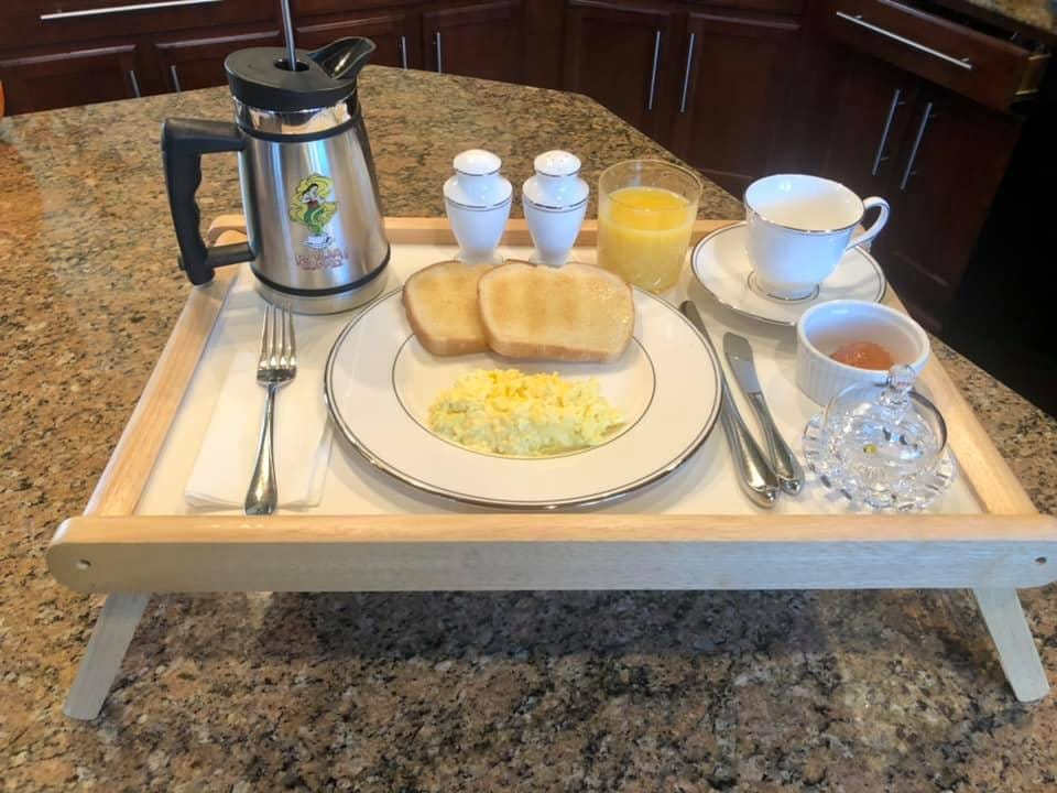 Breakfast of scrambled eggs, toast, coffee, and orange juice, served on china and crystal, arranged on a tray