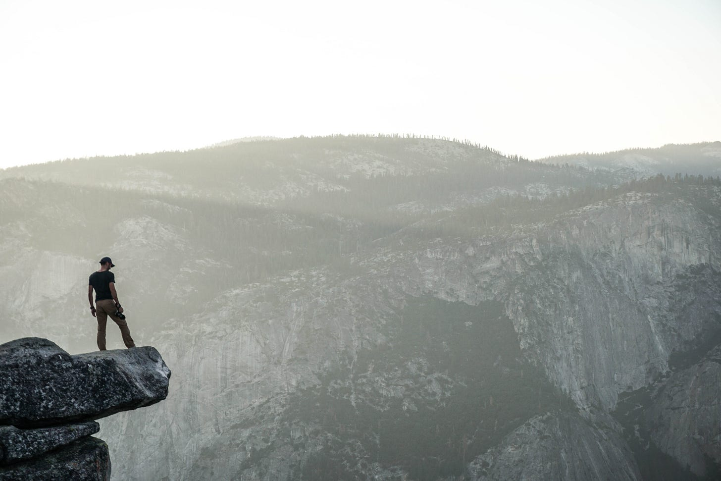 Person standing on ledge in mountains