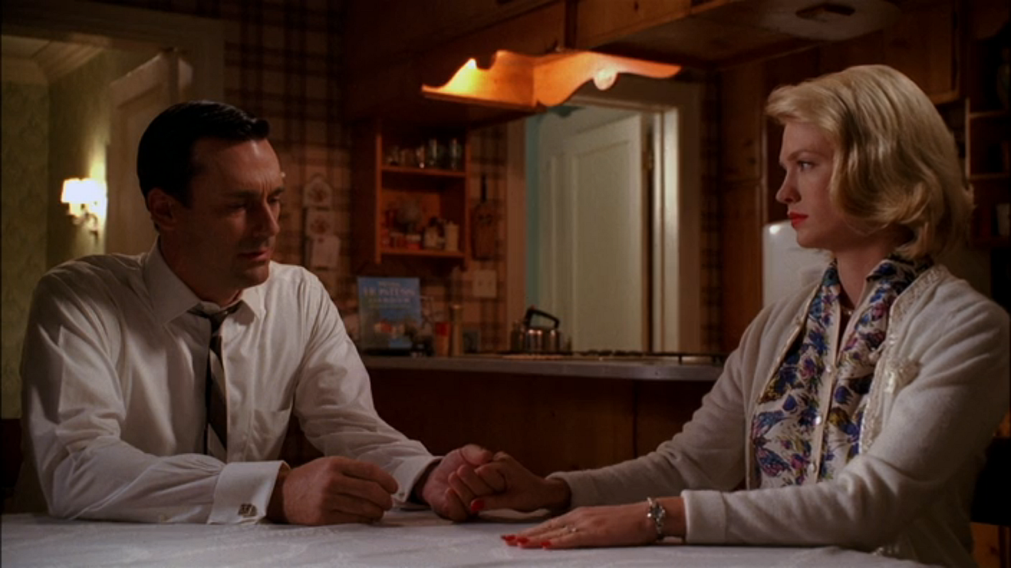 Don and Betty (Jon Hamm and January Jones) hold hands in Season 2 Episode 13 of Mad Men, Meditations in an Emergency