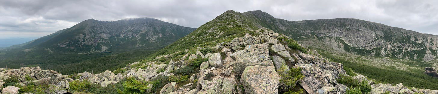 A panorama of Katahdin and Hamlin peak taken from midway up Hamlin ridge, about 3640 ft elevation, facing west. On the left are Pamola peak and Baxter peak above the South Basin, with the knife edge connecting them. In the middle is the spine of Hamlin ridge leading to Hamlin peak at center, and to the right is the North Basin surrounded by its wall of cliffs. The clouds are low and heavy, and the air is hazy from West Coast wildfire smoke.