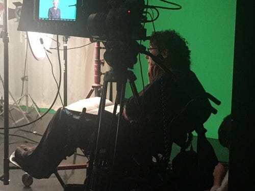 Writer Susan Nussbaum, sitting in a chair by a green screen, as a film is being made in front of her.