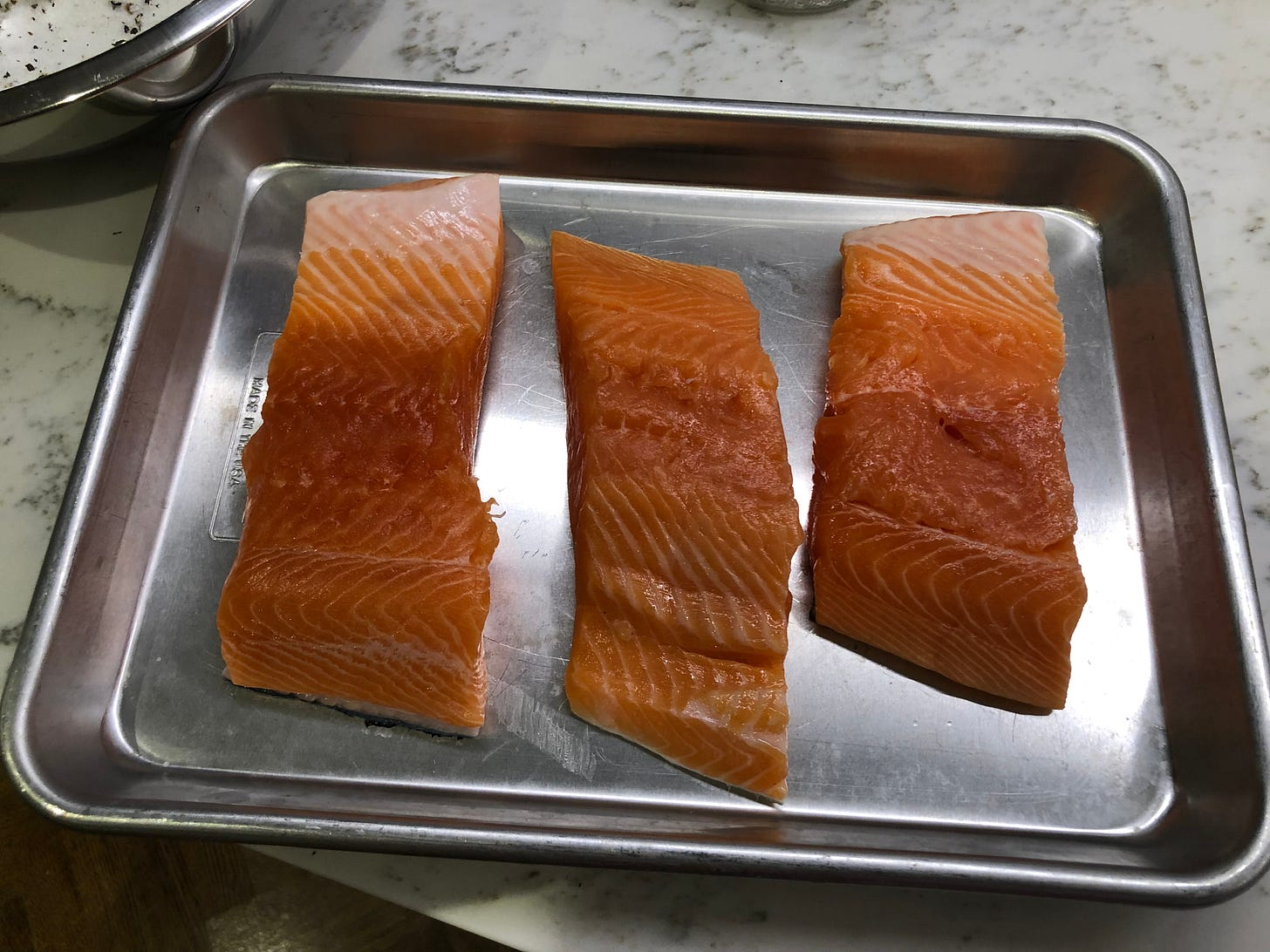 Three pieces of salmon on a metal tray