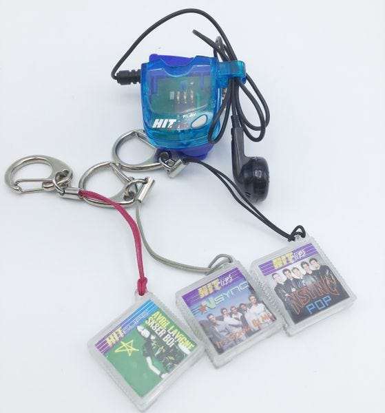 A small, plastic HitClips player, with a single earbud wired to it, with three cartridges for *NSYNC and Avril Lavigne songs.