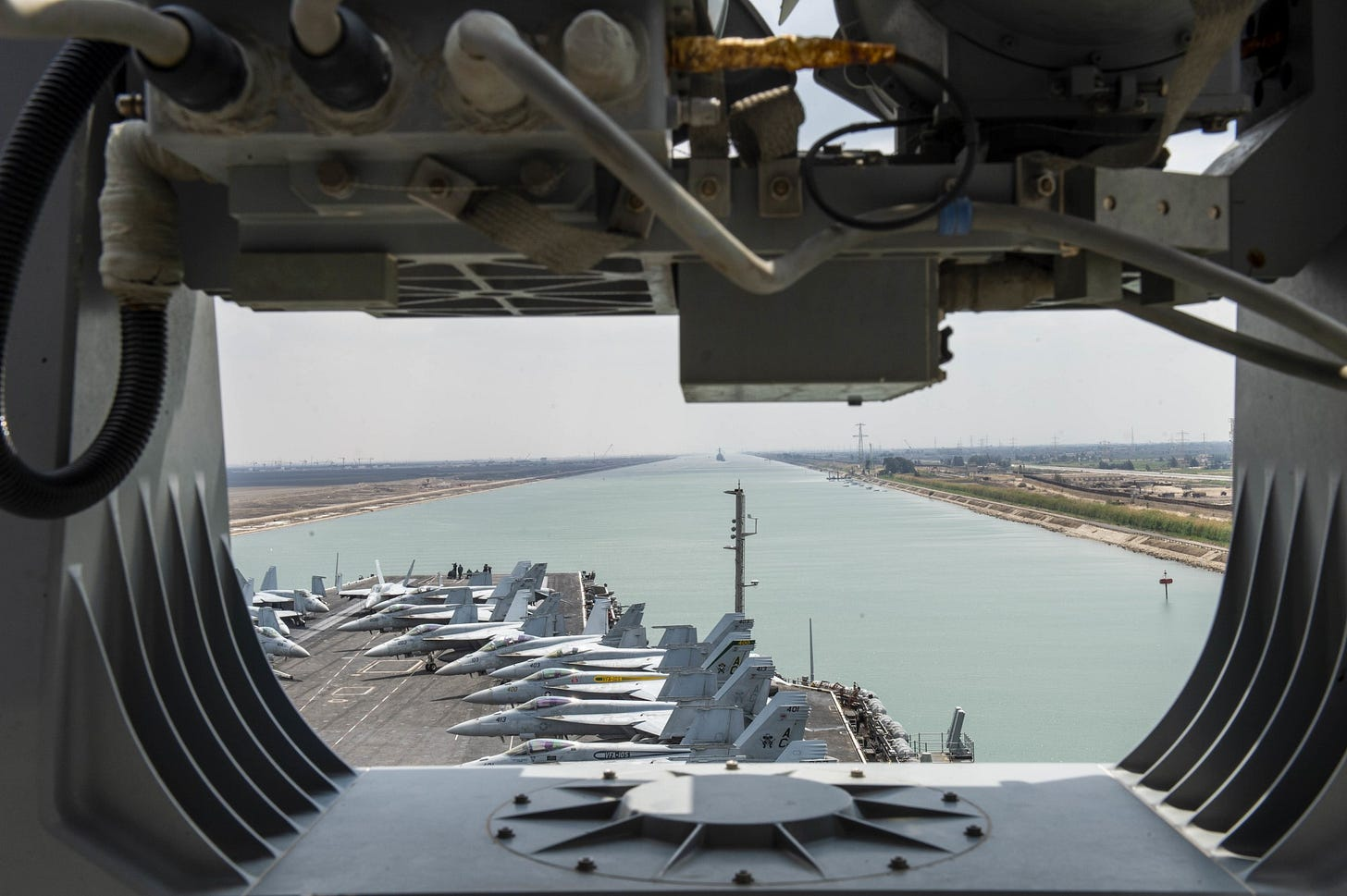 An aircraft carrier transits the Suez Canal. It has many planes on deck.