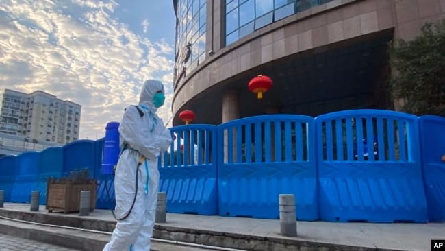 A worker in protective clothing and carrying disinfecting equipment walks outside the Wuhan Central Hospital in Wuhan, China on Feb. 6, 2021.