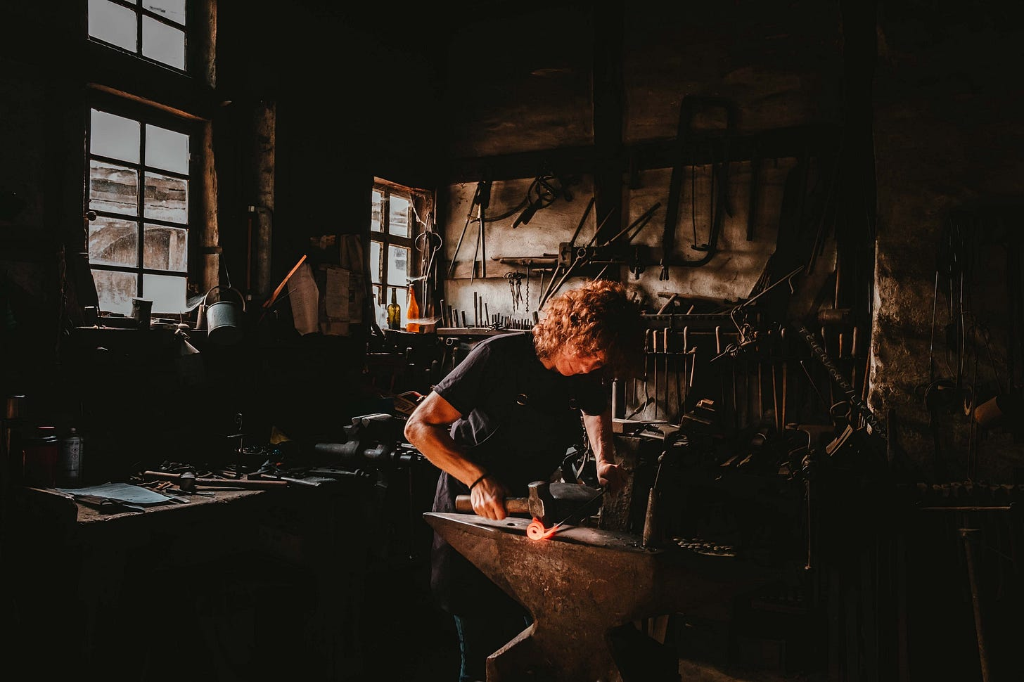 image of a blacksmith working in a workshop for article by Larry G. Maguire
