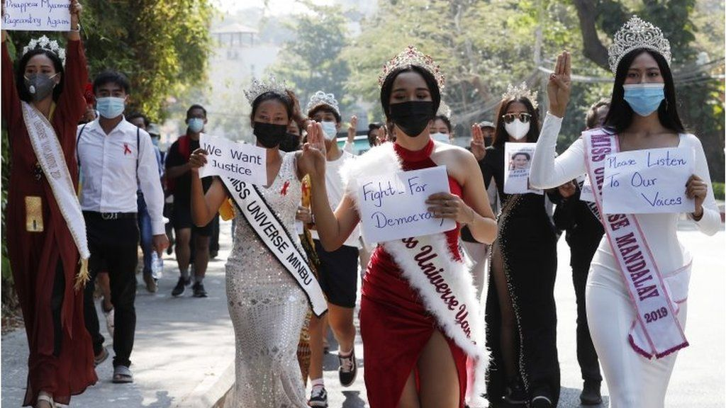 Participants of beauty pageants flash the three-finger salute and hold placards as they march in front of the US Embassy during a protest against the military coup, in Yangon, Myanmar, 10 February 2021