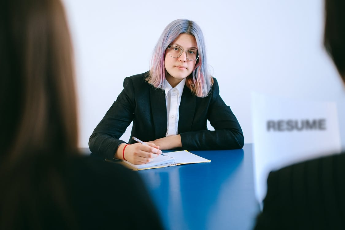 Woman in Black Blazer Sitting by the Table