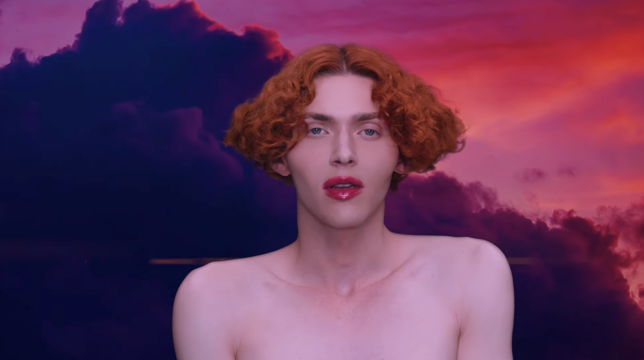 """image of the artist SOPHIE from the video for """"it's okay to cry,"""" facing the camera with bare shoulders and bright red lipstick that matches the cloudy sky in the background"""