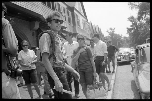 Bob Dylan, with bullwhip and sunglasses, walking on the sidewalk, Newport  Folk Festival: View from stage right, with stands in the background, July  27, 1963